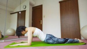 ピラティスのスフィンクスポジションから胸椎を丸める女性