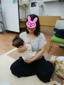 座って赤ちゃんを抱っこするお母さん