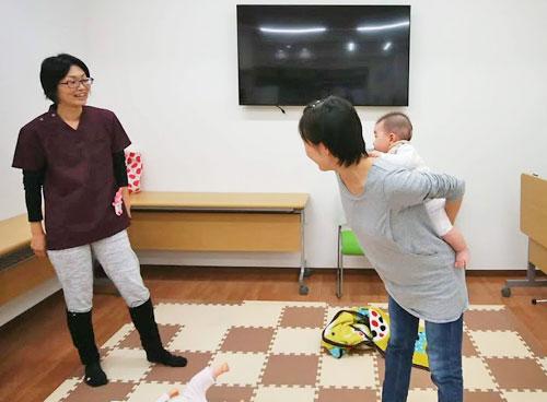お母さんがおんぶの練習をしているところ